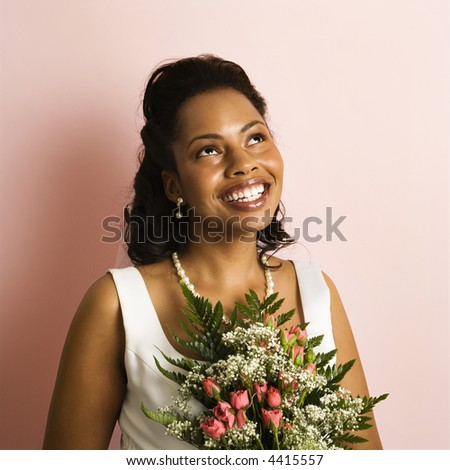 Portrait of a mid-adult African-American bride on pink background. - stock photo
