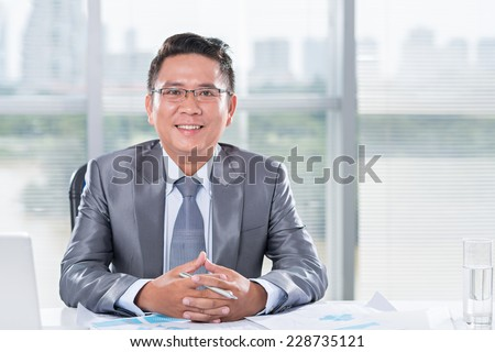 Portrait of a mid-adult businessman smiling at camera - stock photo