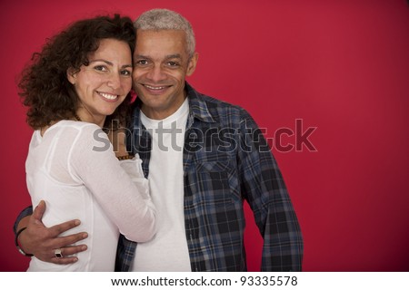 portrait of a mid adult couple hugging on red background - stock photo