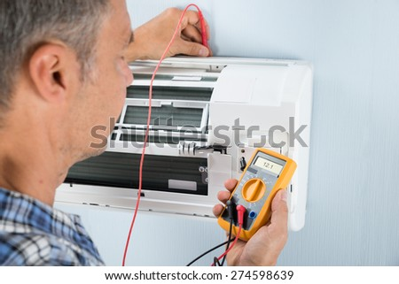 Portrait Of A Mid-adult Male Technician Testing Air Conditioner With Digital Multimeter - stock photo