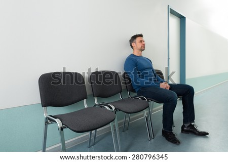Portrait Of A Mid-adult Man Sitting On Chair In Hospital - stock photo