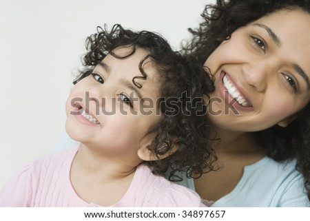 Portrait of a mid adult woman with her daughter smiling - stock photo