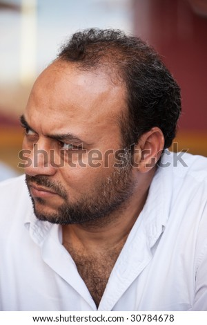 portrait of a mid age egyptian man listening with attention - stock ...
