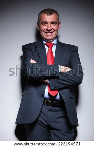Portrait of a mid aged business man leaning on a grey wall with his arms crossed, smiling for the camera. - stock photo