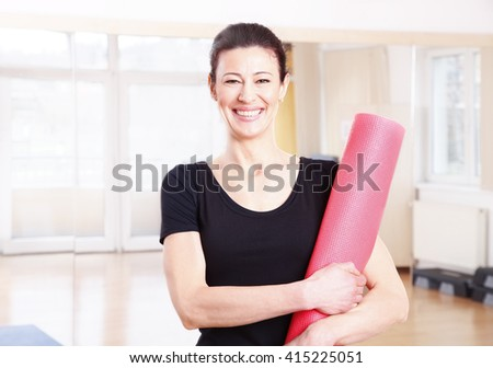 Portrait of a middle age woman holding her yoga mat while standing at yoga studio after workout.  - stock photo
