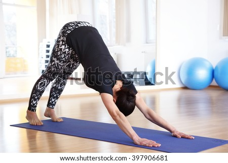 Portrait of a middle age woman in a yoga pose at the studio. - stock photo