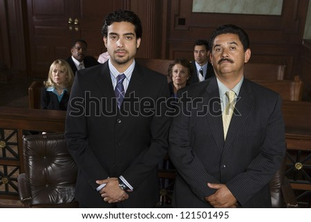 Portrait of a middle aged advocate standing with client and people in the background - stock photo