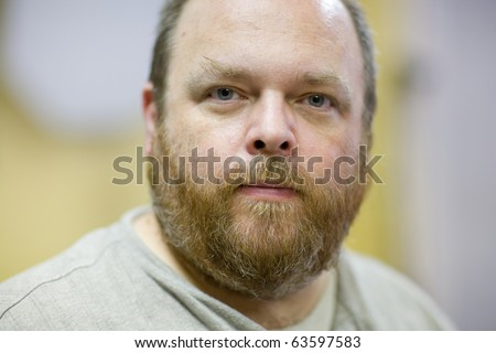 Portrait of a middle aged and obese bearded man.