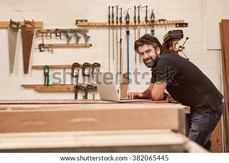 Portrait of a middle-aged artisan in his woodwork workshop with tools on the wall, leaning on his workbench and smiling at the camera while using a laptop - stock photo