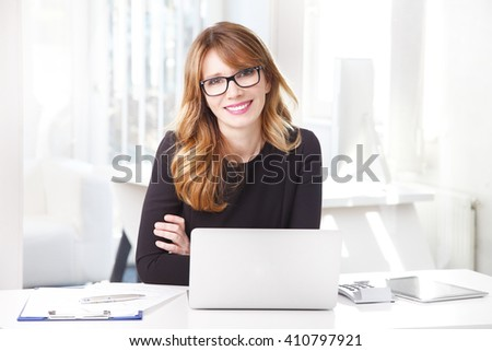 Portrait of a middle aged attractive businesswoman sitting in front of laptop at her desk in an office while looking at camera and smiling.