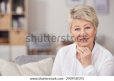 Portrait of a Middle Aged Blond Woman Sitting on the Sofa at Living Room, Looking at the Camera with Hand on the Chin. - stock photo