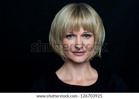 Portrait of a middle aged blonde woman. Isolated against black background. - stock photo