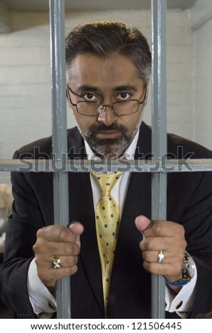 Portrait of a middle aged businessman behind prison gate holding bars - stock photo