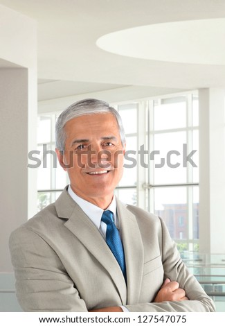 Portrait of a middle aged businessman wearing a light tan suit with his arms folded in a modern office setting. Vertical format, with the man smiling. - stock photo
