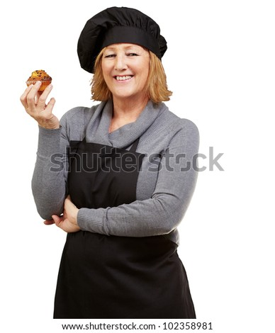 portrait of a middle aged cook woman holding a delicious homemade muffin over a white background - stock photo
