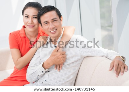 Portrait of a middle-aged couple bonding on the sofa and looking at camera - stock photo