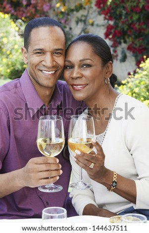 Portrait of a middle aged couple celebrating with white wine outdoors - stock photo