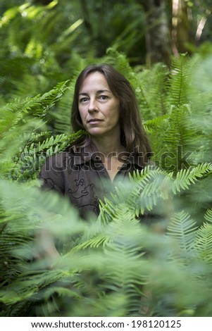 Portrait of a middle aged female hiker surrounded by ferns. - stock photo