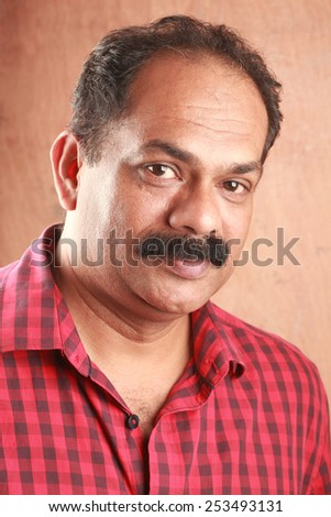 Portrait of a middle aged Indian with wooden background