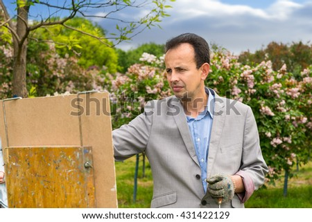 Portrait of a middle-aged male painter wearing a glove in the process outdoors painting his masterpiece - stock photo