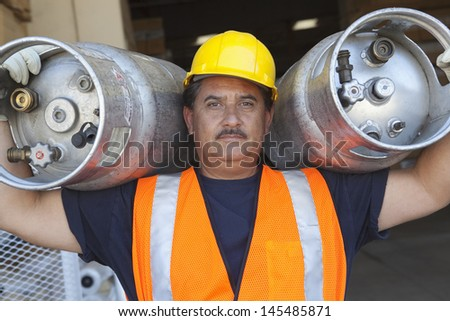 Portrait of a middle-aged man carrying cylinder