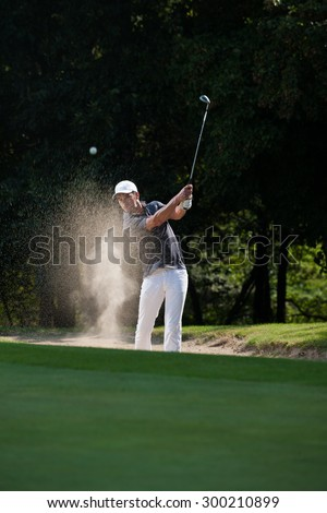 Portrait of a middle aged man trying to shoot his ball out of the bunker, He is playing golf with a white cap and the sand is flying around him - stock photo