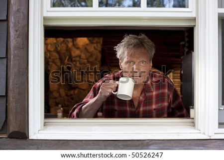 Portrait of a middle-aged man with a plaid shirt, staring out an open window and holding a coffee cup. The image is shot from outside the window, and he is looking at the camera. Horizontal format. - stock photo