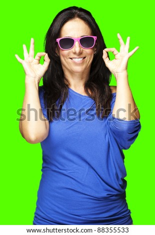 portrait of a middle aged woman gesturing good symbol against a removable chroma key background - stock photo