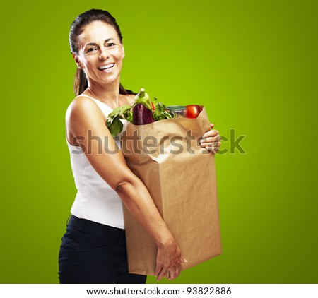 portrait of a middle aged woman holding the purchase over a green background - stock photo