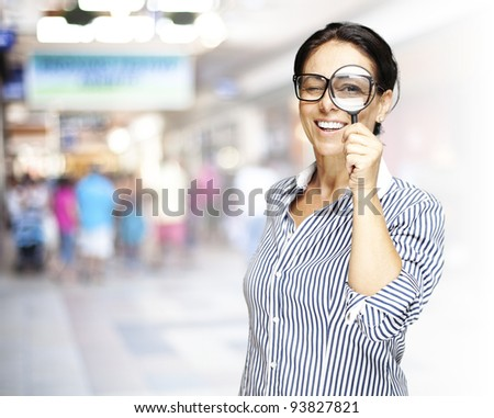 portrait of a middle aged woman looking through a magnifying glass against a crowded place - stock photo