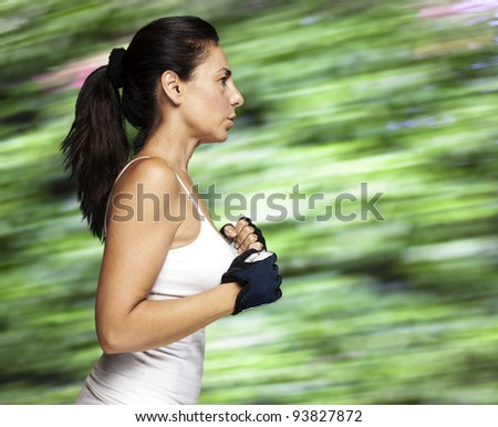 portrait of a middle aged woman running against a nature background - stock photo
