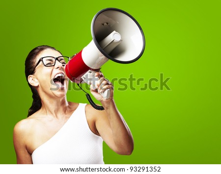 portrait of a middle aged woman shouting using a megaphone over a green background - stock photo