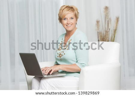 Portrait of a middle aged woman sitting on sofa using laptop and looking to camera