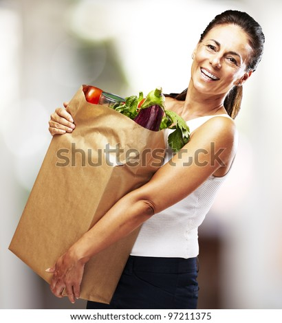 portrait of a middle aged woman smiling and carrying the purchase indoor - stock photo