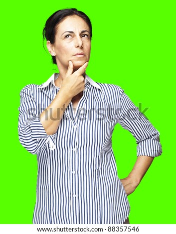 portrait of a middle aged woman thinking against a removable chroma key background - stock photo