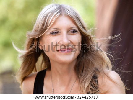 Portrait of a Middle-aged Woman with Blond Hair Smiling - stock photo