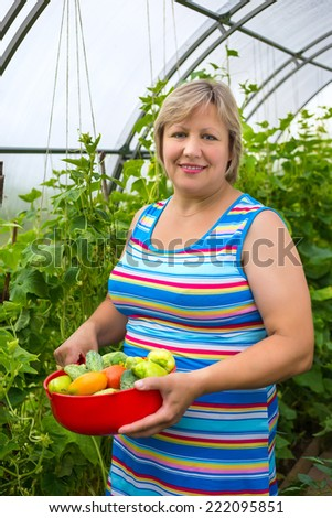 Portrait of a middle-aged woman with vegetables in a bowl near greenhouses - stock photo