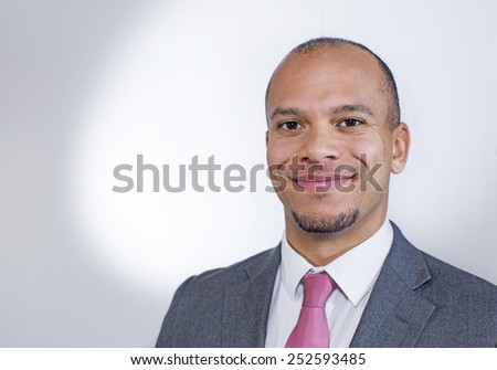 Portrait of a mixed race young businessman smiling to camera with a faded colour background - stock photo