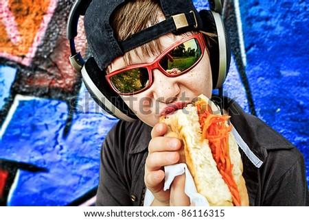Portrait of a modern boy teenager eating hot dog outdoors. - stock photo