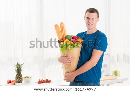 Portrait of a modern guy holding a paper bag with groceries - stock photo