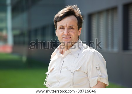 Portrait of a modern middle-aged man with a building on the background - stock photo