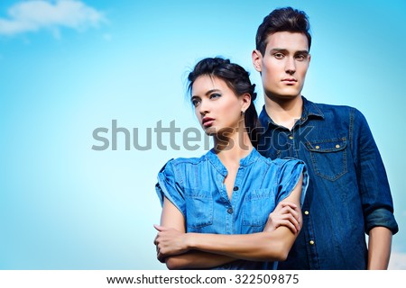 Portrait of a modern young people wearing jeans clothes over blue sky. Fashion shot. - stock photo