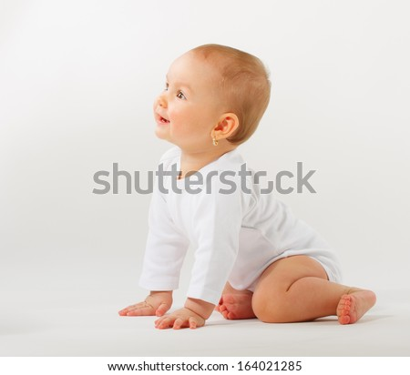 Portrait of a 9 month baby girl on a blue painted background - stock photo