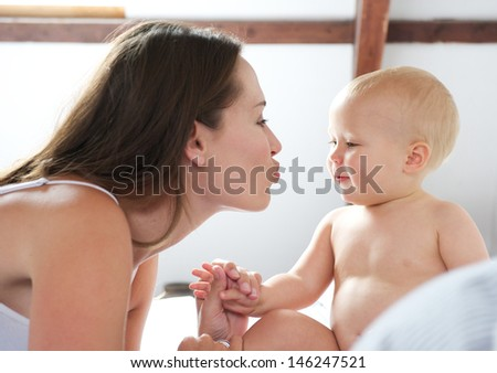 Portrait of a mother and cute baby playing on bed