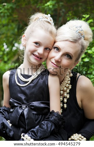 Portrait of a mother and daughter dressed in elegant little black dresses and pearls.