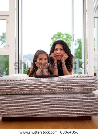 Portrait of a mother and daughter in home interior looking at the camera with their heads leaning on hands - stock photo