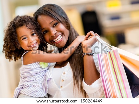 Portrait of a mother and daughter shopping and looking happy  - stock photo