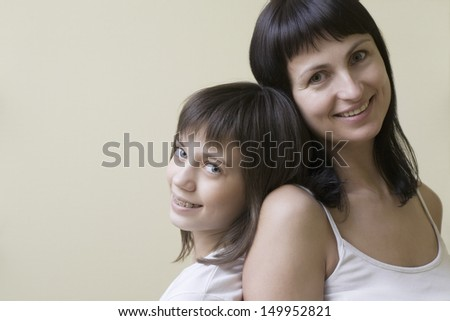 Portrait of a mother and daughter smiling against colored background - stock photo