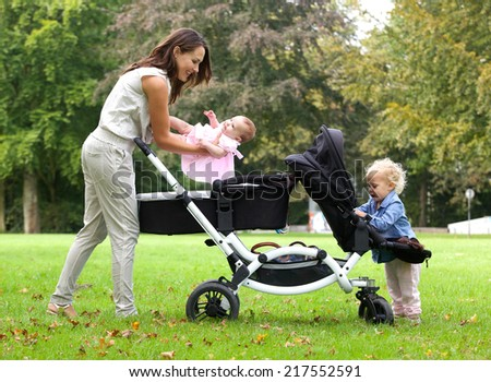 Portrait of a mother and daughters with pram outdoors - stock photo