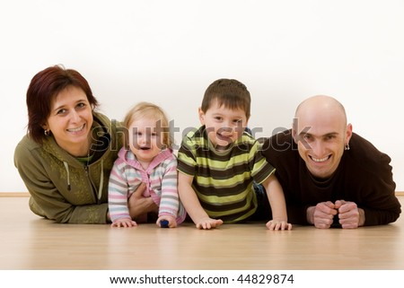 Portrait of a mother and father and two children lying on the floor. - stock photo